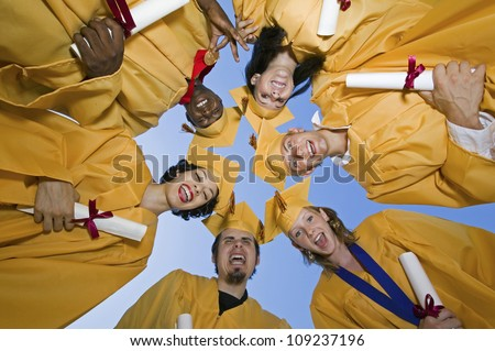 Group of multiethnic graduates with certificates forming huddle against sky - stock photo