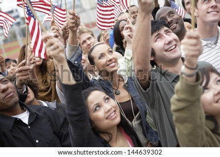 Group of multiethnic people holding up American flags - stock photo