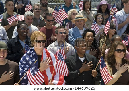 Group of multiethnic people singing American national anthem and holding American flags - stock photo