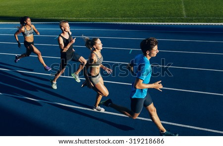 Group of multiracial athletes practicing running on racetrack. Male and female athletes during running session at athletics stadium. - stock photo