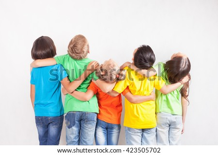Group of multiracial funny children. Kids looking up at copy space with white background. Dressed in colorful T-shirts and jeans. Education, school - stock photo