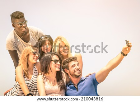 Group of multiracial happy friends taking a selfie outdoors - International concept of happiness and multi ethnic friendship all together against racism for peace and fun - Vintage filtered look - stock photo