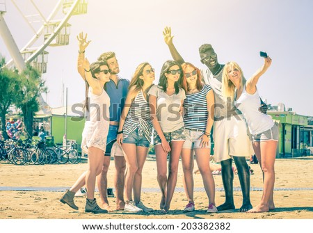 Group of multiracial happy friends taking selfie at ferris wheel - International concept of happiness and multi ethnic friendship all together against racism for peace and fun - Vintage filtered look - stock photo