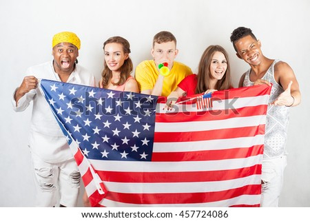 Group of multiracial people holding a american flag. International people. United States of America. Elections. International games at Rio de Janeiro, Brazil. Happy fans. Multi-ethnic person. Fan zone - stock photo