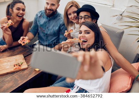 Group of multiracial young people taking a selfie while eating pizza. Young woman eating pizza her friends sitting around during a party. - stock photo