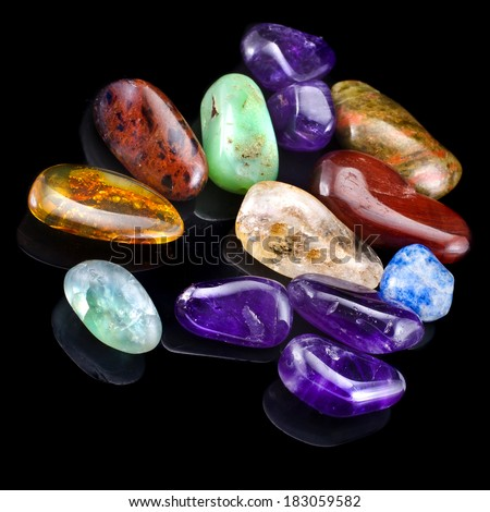 Group of natural colorful raw gemstones on black  background  - stock photo