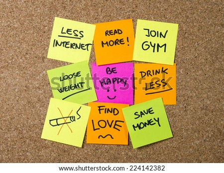 Group of New year Resolution Notes on pink, yellow, orange and green on cork board written with message of diet, join gym, find love, quit smoking and be happy - stock photo