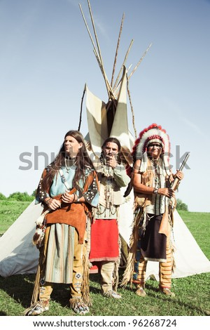 Group of North American Indians about a wigwam - stock photo