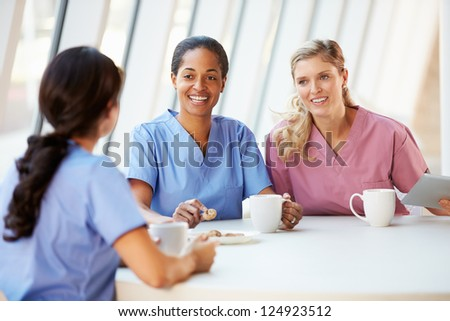Group Of Nurses Chatting In Modern Hospital Canteen - stock photo