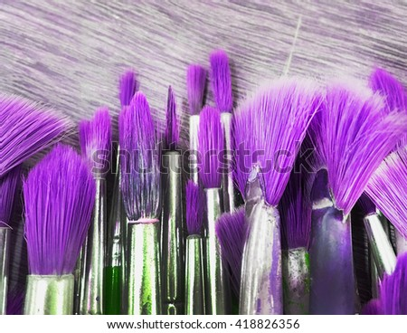 Group of old paint blushes on wooden in purple tone - stock photo