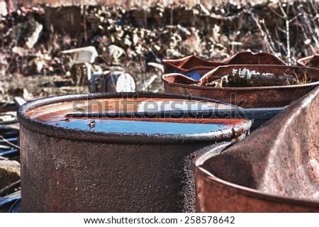 Group of old, rusty barrels with toxic chemical  waste. Photo was taken on place, where textile factory was wrong  demolished. Hdr photo.   - stock photo