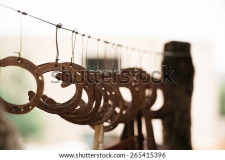 Group of old rusty metal horseshoes hanging. - stock photo