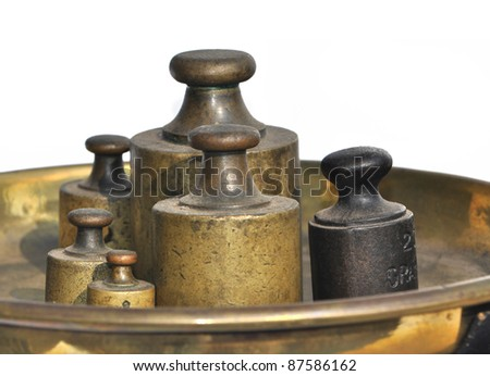 Group of old weights on bronze scale - stock photo