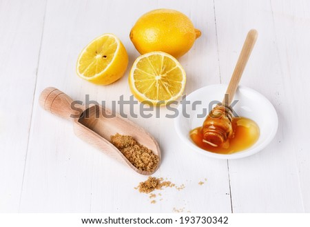 Group of organic lemons with honey and brown sugar over white wooden background  - stock photo