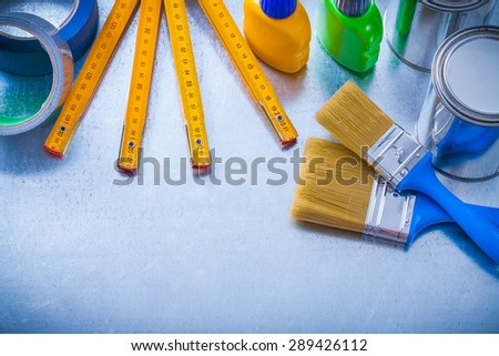 Group of paint objects with duct tapes and wooden meter on metallic background construction concept. - stock photo
