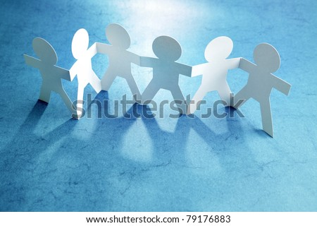 Group of paper chain people holding hands together. Teamwork concept - stock photo