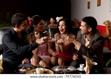 group of party lounge friends feeding young woman - stock photo