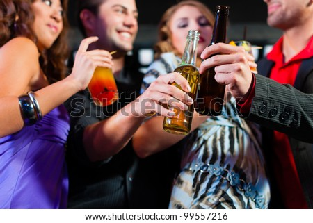 Group of party people - here two couples - with cocktails and beer in a bar or club having fun - stock photo