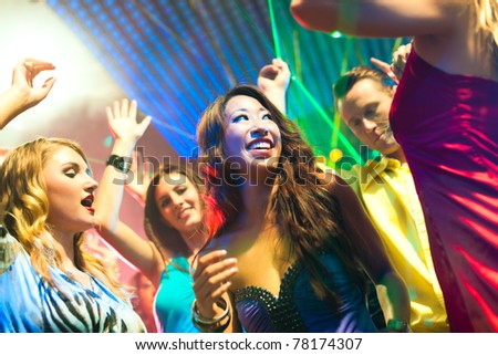 Group of party people - men and women - dancing in a disco club to the music - stock photo