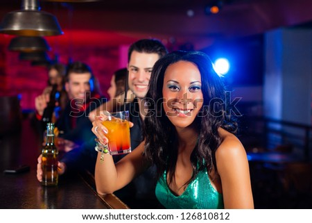 Group of party people with cocktails in a bar or club having fun, one woman is looking into the camera - stock photo