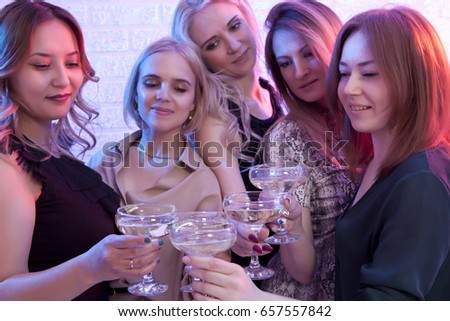 Group of partying girls clinking flutes with sparkling wine. Focus on glasses