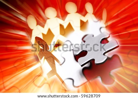 Group of people and last piece of jigsaw puzzle - stock photo