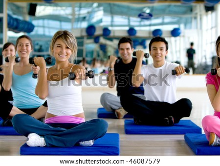Group of people at a gym class lifting free-weights - stock photo