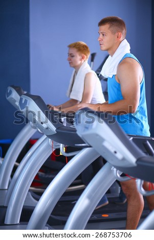 Group of people at the gym exercising on cross trainers - stock photo