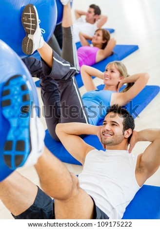 Group of people at the gym in a Pilates class - stock photo