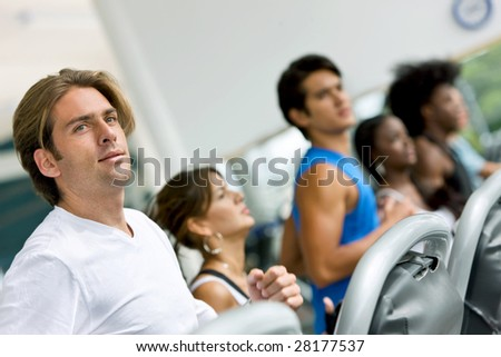 group of people at the gym on cardio machines