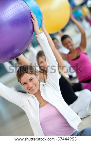 Group of people at the gym smiling with a pilates ball - stock photo