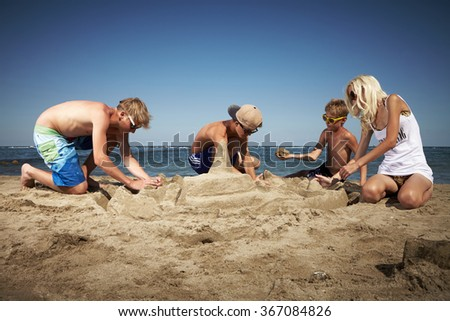 Group of people building sand castle on beach by the sea