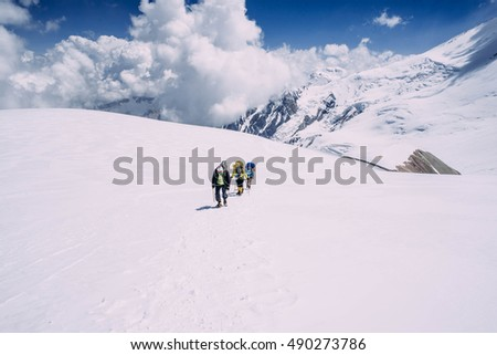group of people climbing in high mountains