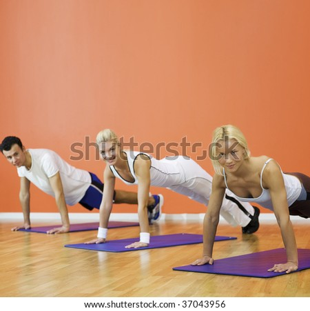 Group of people completing push ups - stock photo