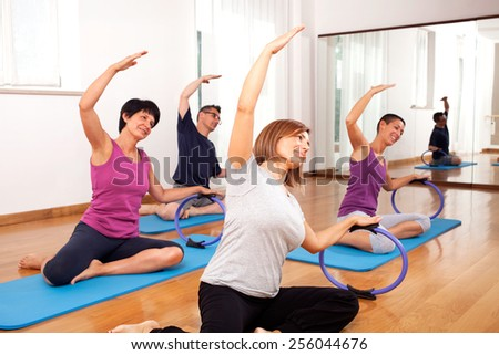 group of people copying fitness exercise by the teacher