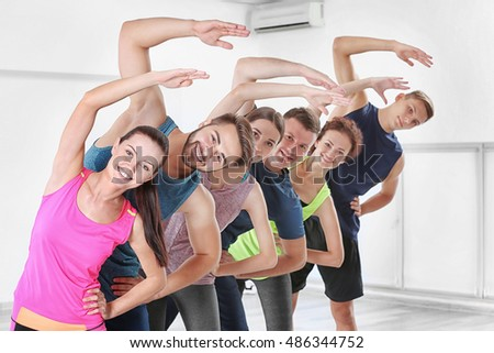 Group of people doing exercises  in gym
