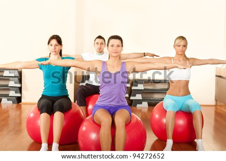 group of people doing  exercises on fitness ball in gym - stock photo