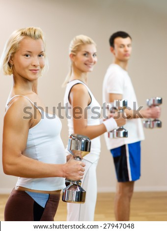 Group of people doing fitness exercise with dumbbells - stock photo