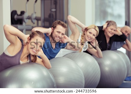 Group of people doing pilates exercises at the gym in a receding diagonal row with focus to the three young people in the foreground with an elder couple behind - stock photo