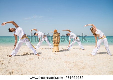 Group of people doing stretching - Capoeira team training on the beach - Martial arts athletes performing stunts - stock photo