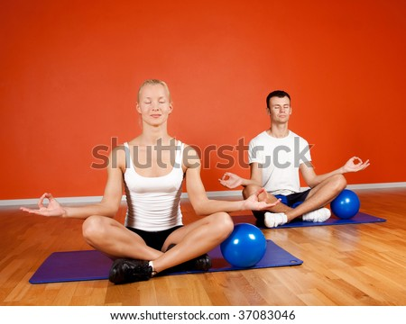 Group of people doing yoga exercise with fitness balls in gym room - stock photo
