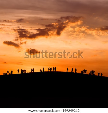 Group of people enjoying the sunset on hill - stock photo