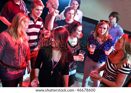 Group of people enjoying themselves on the dance floor - stock photo