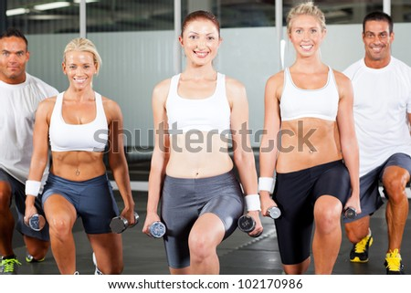 group of people exercise in gym with dumbbells - stock photo