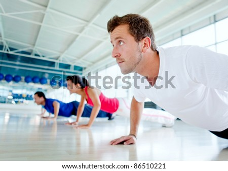Group of people exercising at the gym doing push ups - stock photo