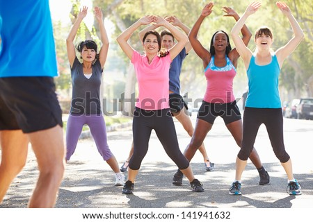 Group Of People Exercising Street With Personal Trainer - stock photo