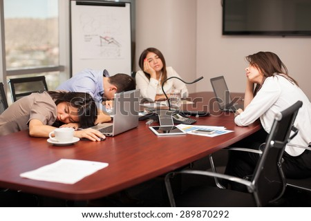 Group of people falling asleep in a meeting room after working too much - stock photo