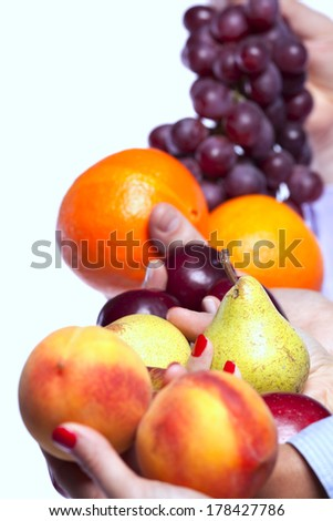 Group of people hands holding apples, oranges, plums, peaches, pears and grapes (selective focus) - stock photo