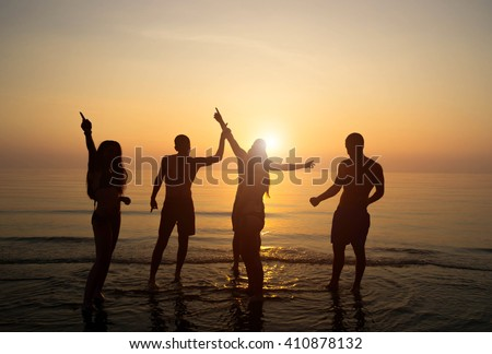Group of people having fun and dancing during a beach party - stock photo