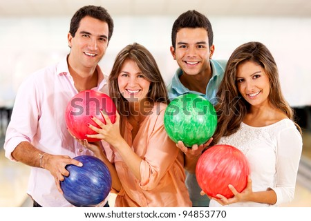 Group of people having fun bowling and smiling